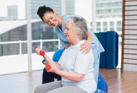 trainer-looking-at-senior-woman-lifting-dumbbells
